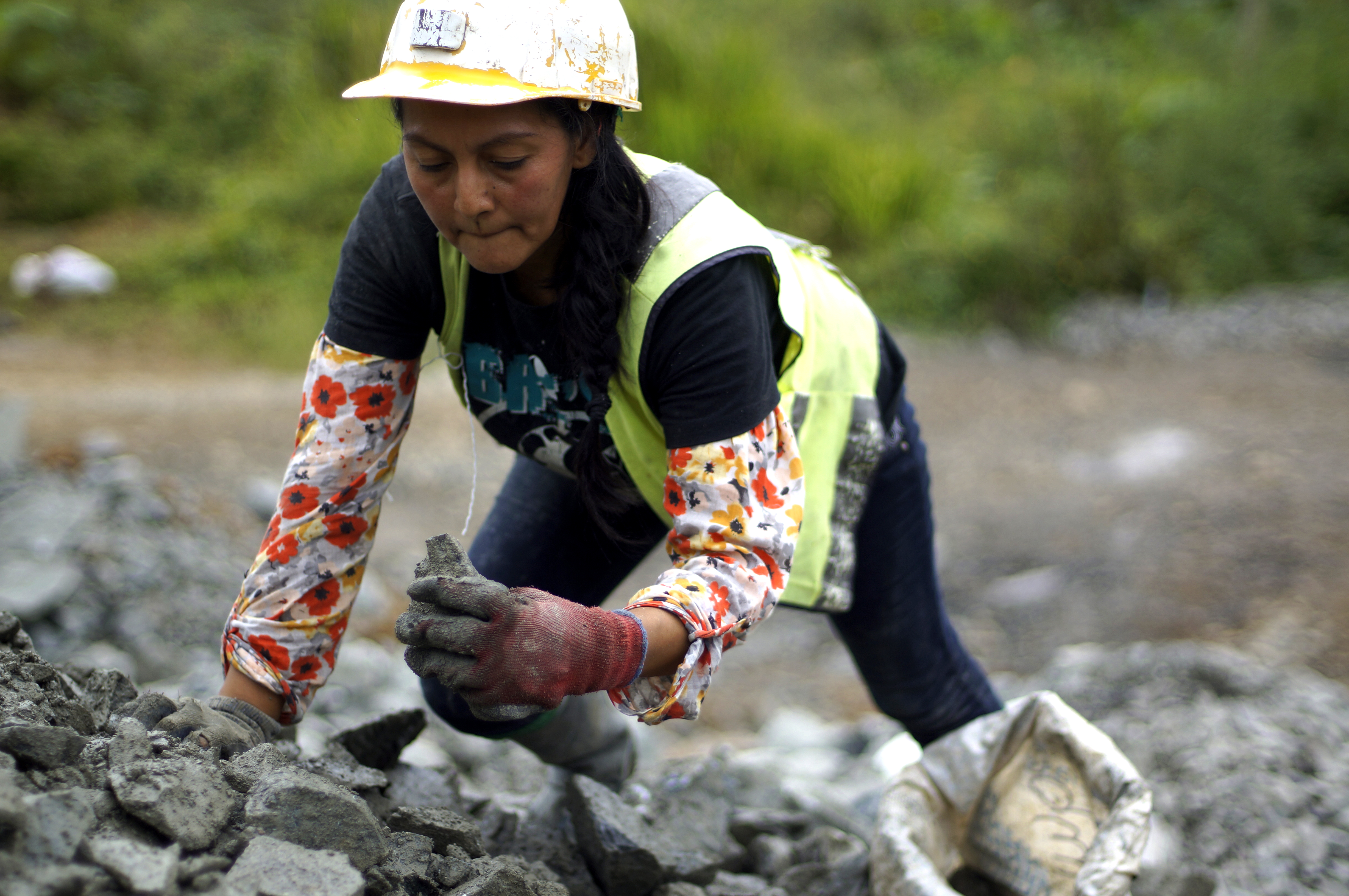 Woman miner in Ecuador sorting through discarded material