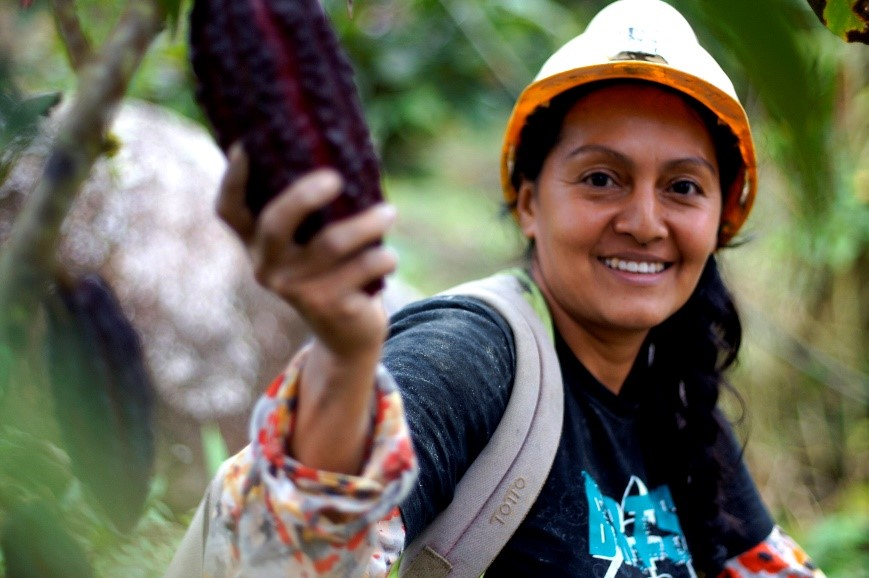 Woman miner from Ecuador with cacao plant