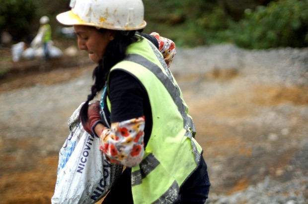 Woman miner in Ecuador carrying a bag of ore