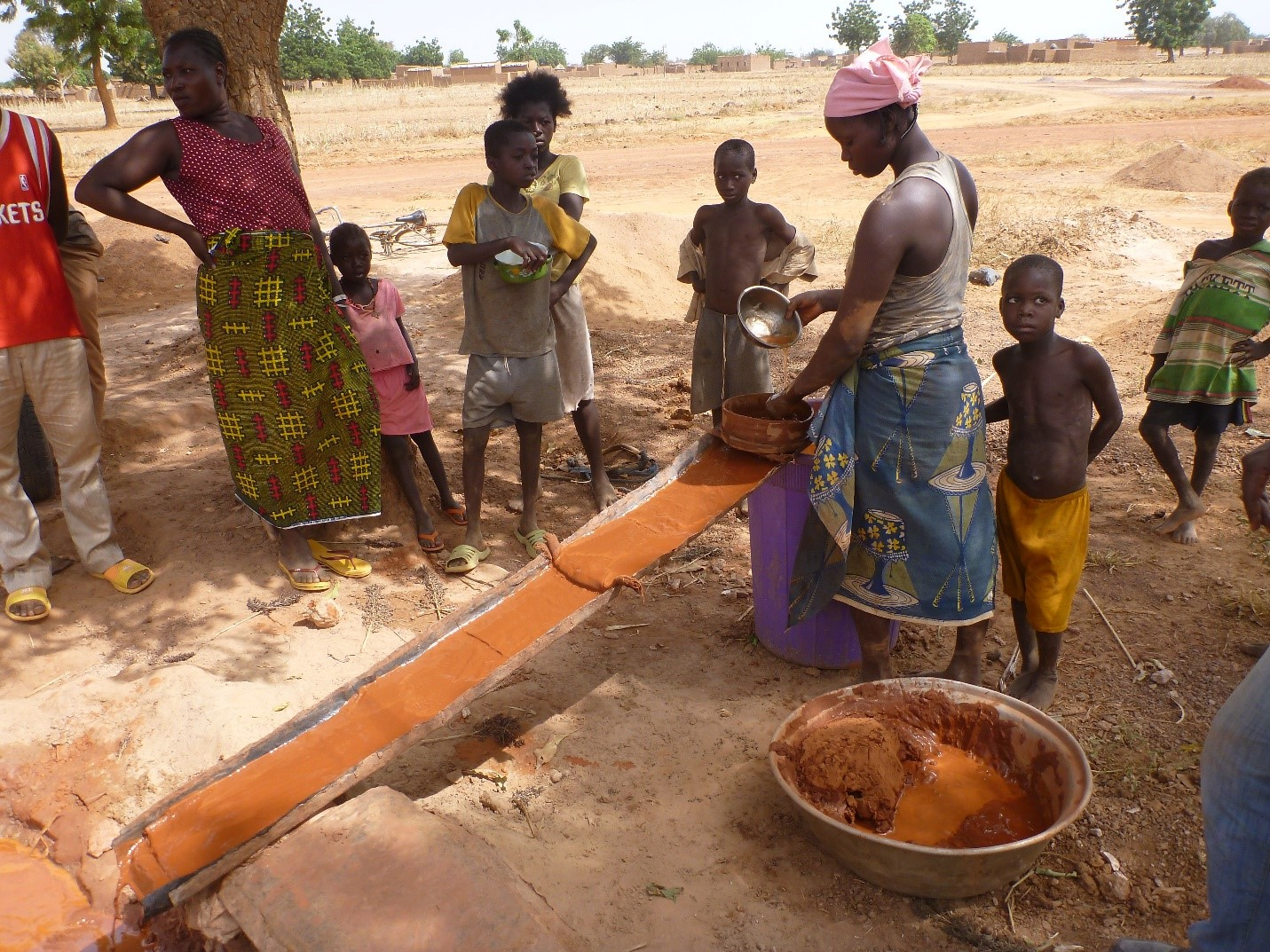 A woman miner performing sluice washing while taking care of young children (Photo credit: Dr. kevin Telmer, Artisanal Gold Council)