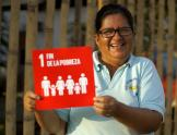 Person holding SDG 1 sign