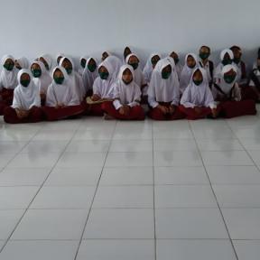 Un grupo de niños en Indonesia se sientan en el suelo para un ejercicio de narración sobre los peligros del mercurio